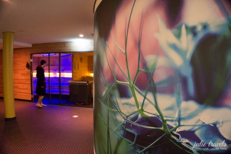 Großer Aufdruck in natürlichen Farben auf einer runden Wand, die Sauna farbig angestrahlt im Hintergrund.