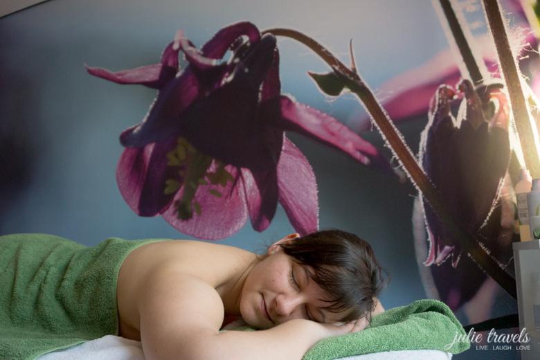 Ich auf einer Liege, total entspannt, vor einer toll bedruckten Wand mit einer Blume.