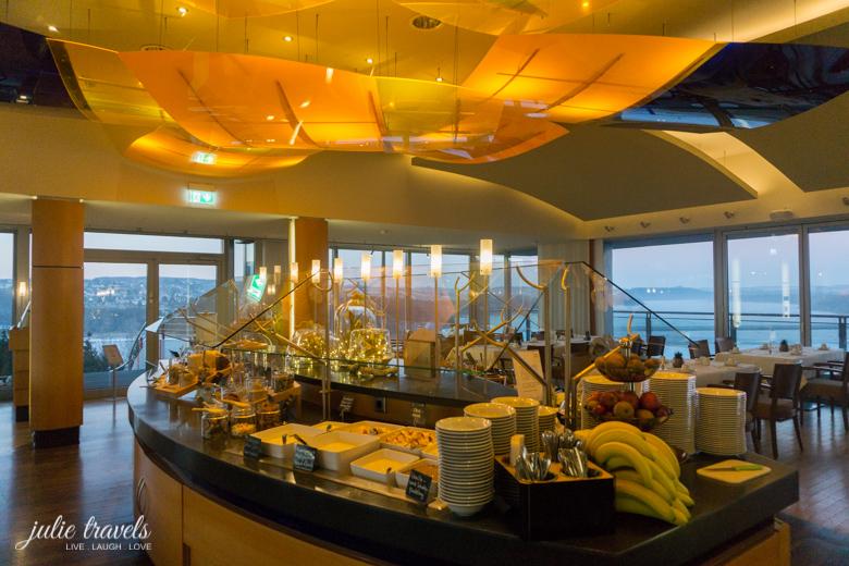 Ovales Buffet im Panorama Restaurant mit gelben Lampen an der Decke, Glasfront im Hintergrund