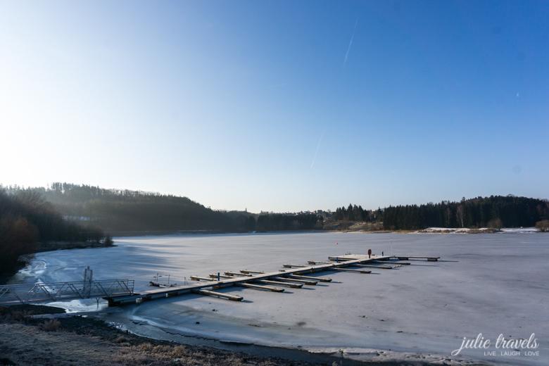 Steg im gefrorenen See, der Wald dunkel im Hintergrund
