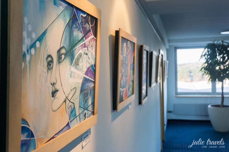 Hotelflur mit in Holz gerahmten Acryl-Bildern an der linken Wand, Fenster und Zimmerpflanze im Hintergrund.