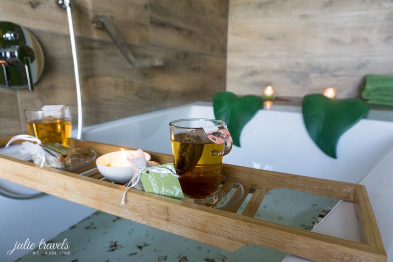 Weiße Badewanne für zwei Personen mit grünen Kopfstützen und Holztablett mit zwei Teetassen.