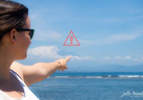 Julia zeigt von der Ferne auf den Vulkan Mount Agung in Bali