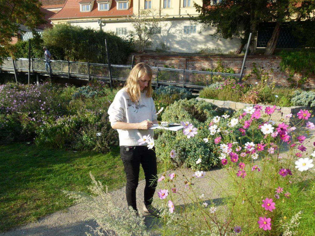 Kristin steht im Park und malt Blumen
