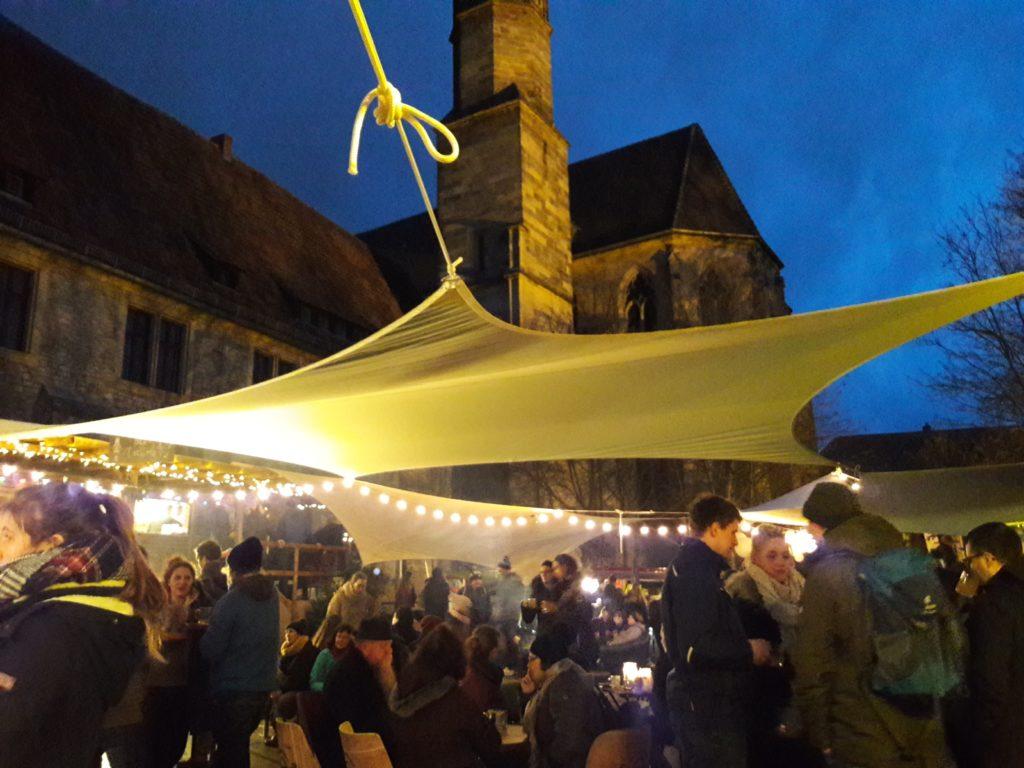 Besucher des Weihnachtsmarktes unter einem Sonnensegel vor der Predigerkirche