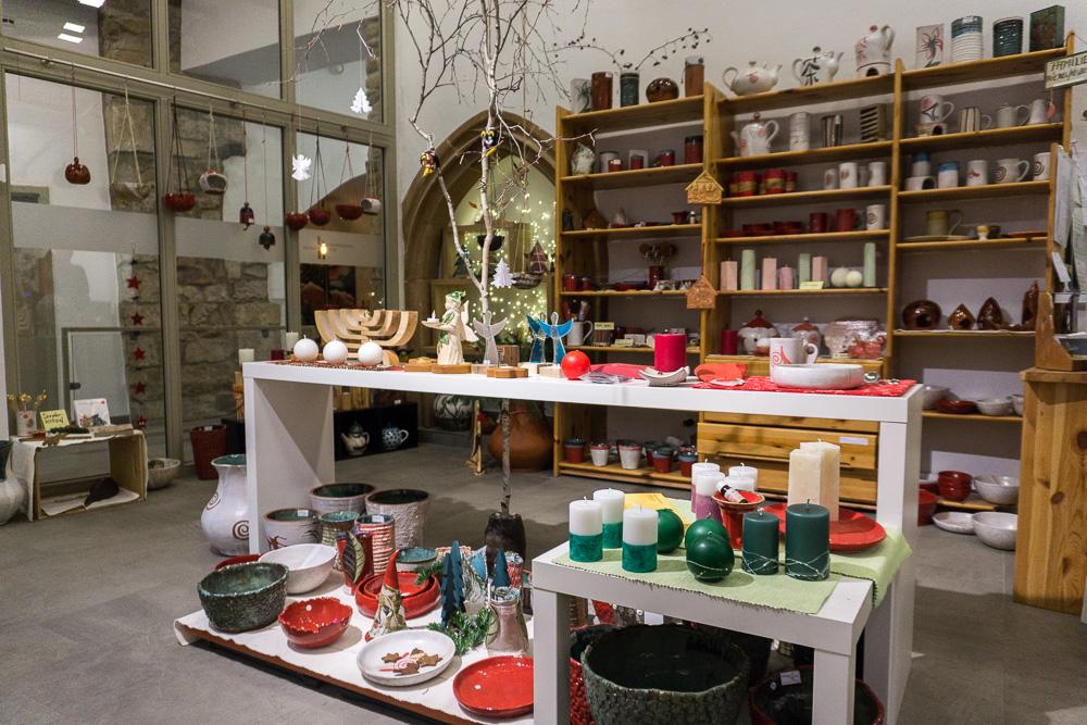 Im Vordergrund Tische mit weihnachtlicher Deko, im Hintergrund Regale mit Kerzen.