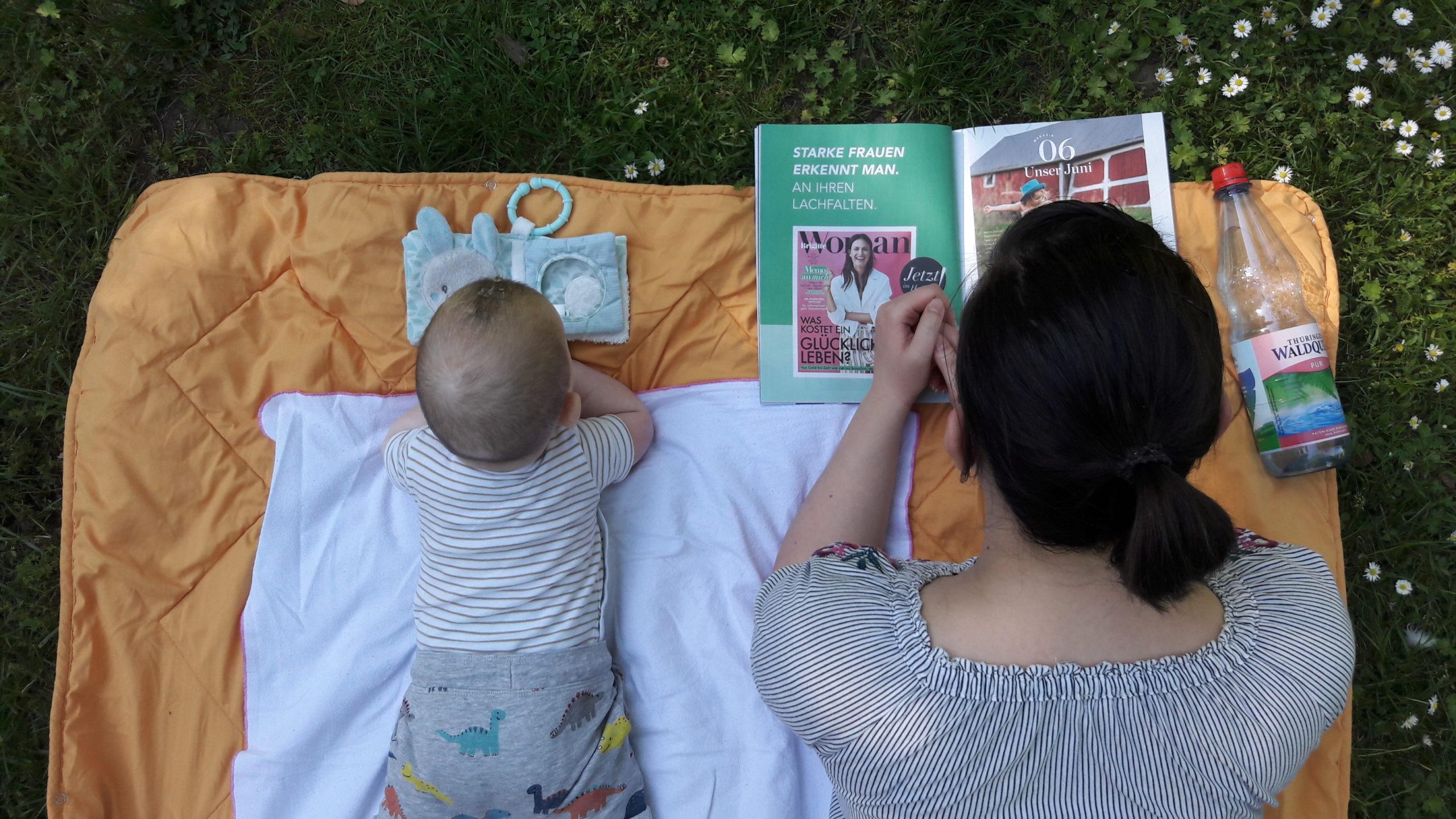 Mutter und Sohn liegen auf dem Bauch auf einer Decke im Park und lesen